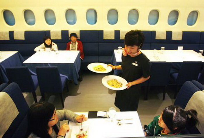 A waitress dressed as a flight attendant serves customers inside the A380 In-flight Kitchen, a restaurant named after the giant Airbus airliner, in Taipei