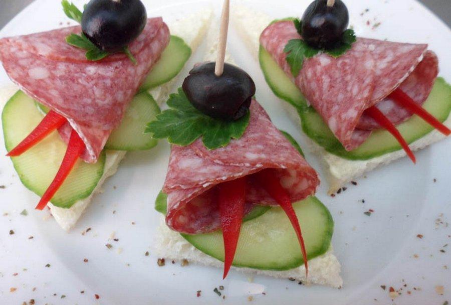 Копчена ковбаса, огірок, болгарський перець, оливка, зелень на шматочку білого хліба.