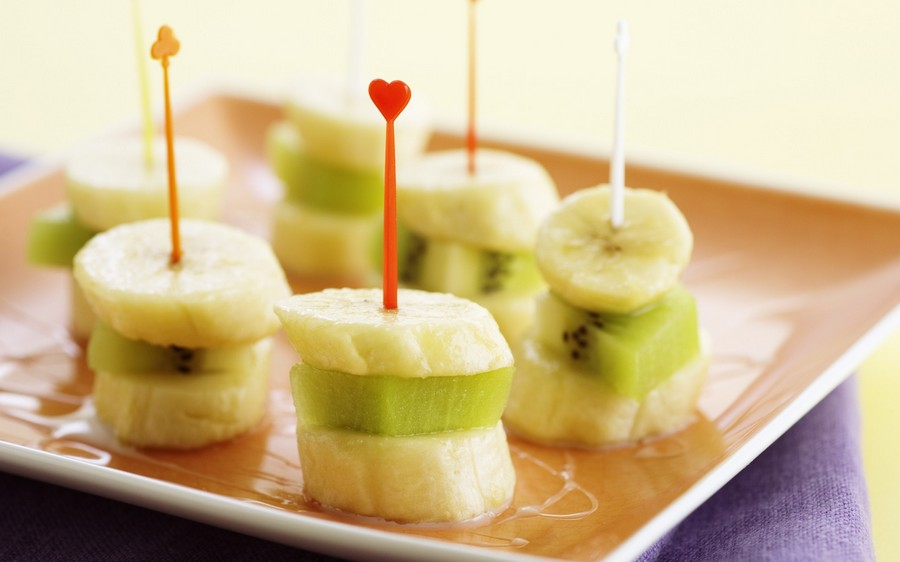 Фруктове канапе: шматочки банана, яблука та ківі на шпажці.