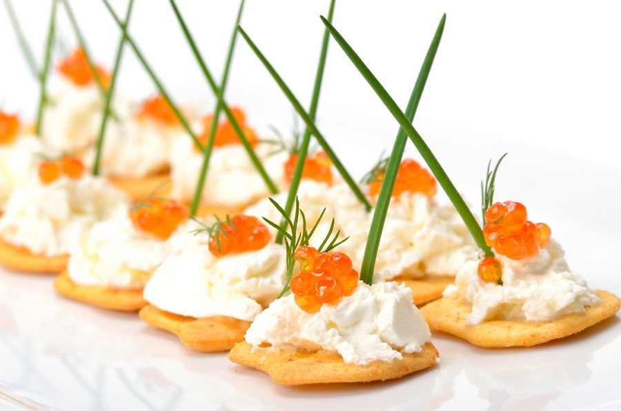 Червона ікра, вершковий крем-сир, гілочка свіжого кропу, перо зеленої цибулі на сирному крекері.