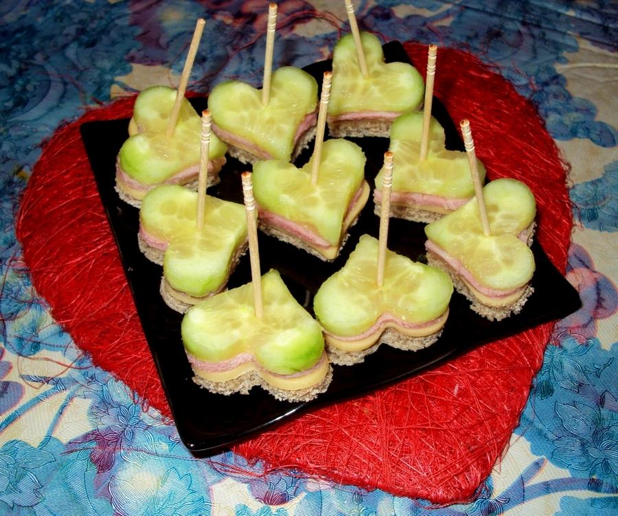 Канапе для романтичного фуршету: ковбаса сир та свіжий огірок на чорному хлібі - усе вирізати формочкою для печива.