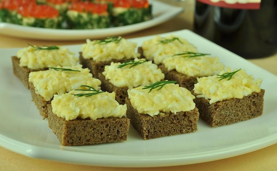 Салат з твердого сиру з вареним яйцем та часником та зеленим кропом н шматочку чорного хліба.