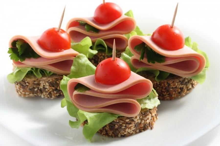 Кружальце вареної кобваси, складене вчетверо, листя салату, зелень петрушки, половинки чері на шматочку чорного хліба.
