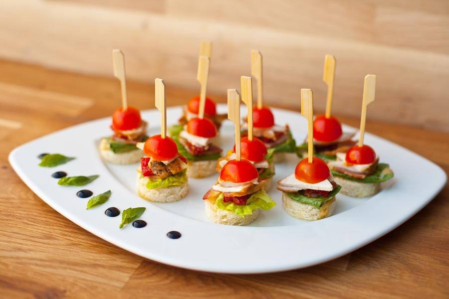 Шматочок смаженої курятини, сир, помідор чері, листя салату на шматочку білого хліба.