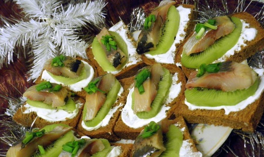Шматочок оселедця, ківі, зелена цибуля на шматочку чорного хліба.
