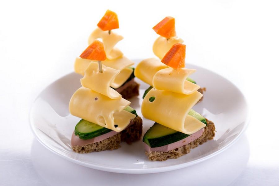 Вітрильники з твердого сиру, моркви, свіжого огірка та ковбаси, встромлені шпажкою у шматочок чорного хліба.