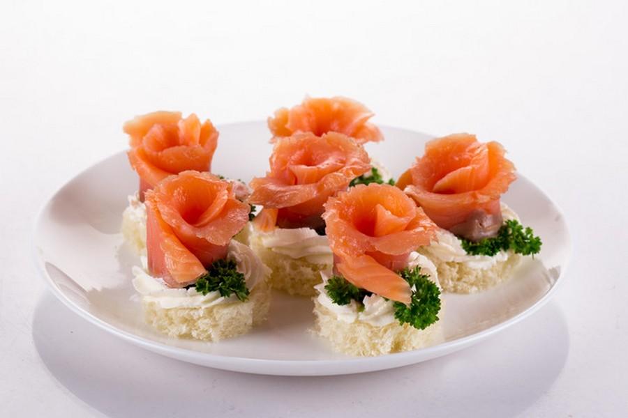 Троянди з червоної слабосоленої риби, вершкового сиру та зелені на шматочках білого хліба або багета.