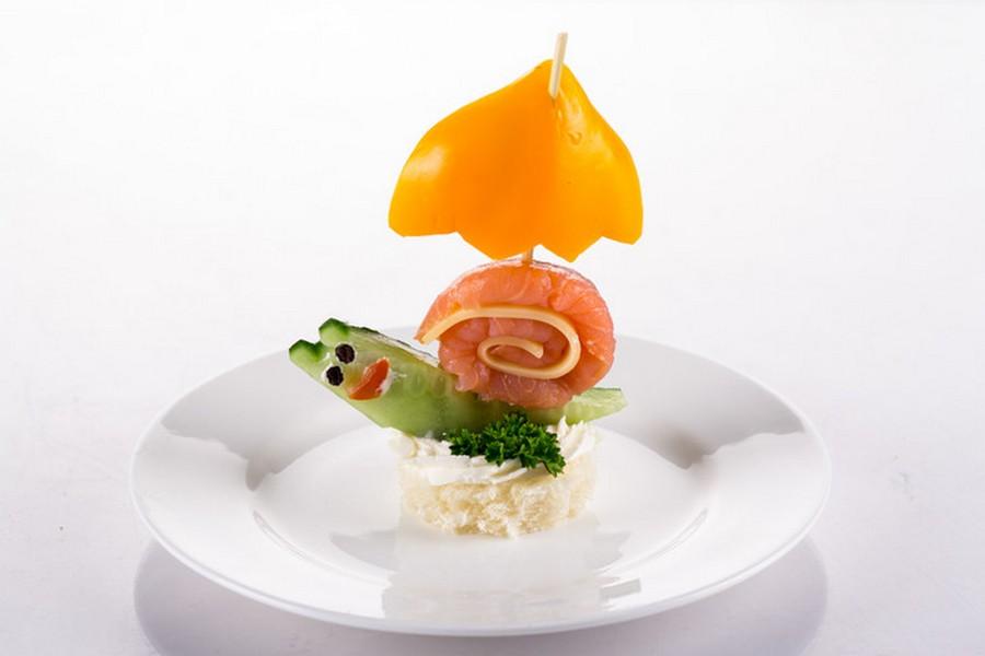 Равлик з огірочка, копченого лосося та твердого сиру на змащеному вершковим сиром шматочку білого хліба, парасолька з болгарського перцю.