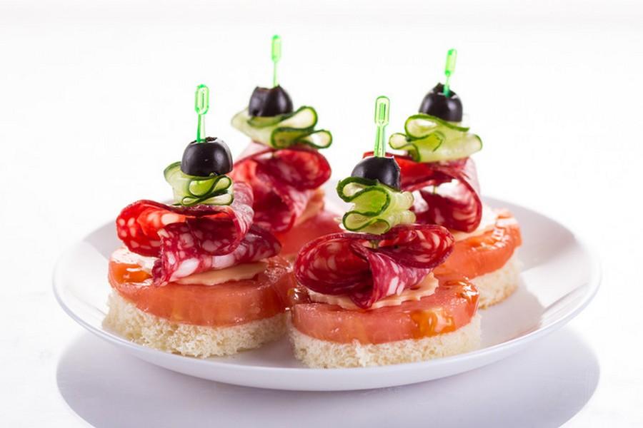 Помідор, копчена ковбаса, твердий сир, огірок, оливка на шматочку білого хліба.