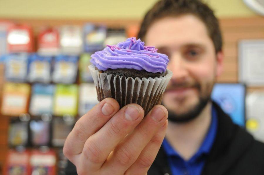 hombre-sosteniendo-un-cupcake-de-chocolate-con-buttercream-morado-ofreciendoselo-a-alguien